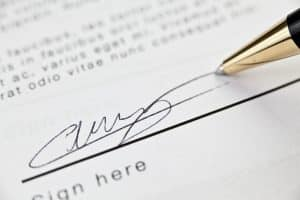 Timing your hiring of a Fairfax or Virginia criminal lawyer- Picture of contract and pen